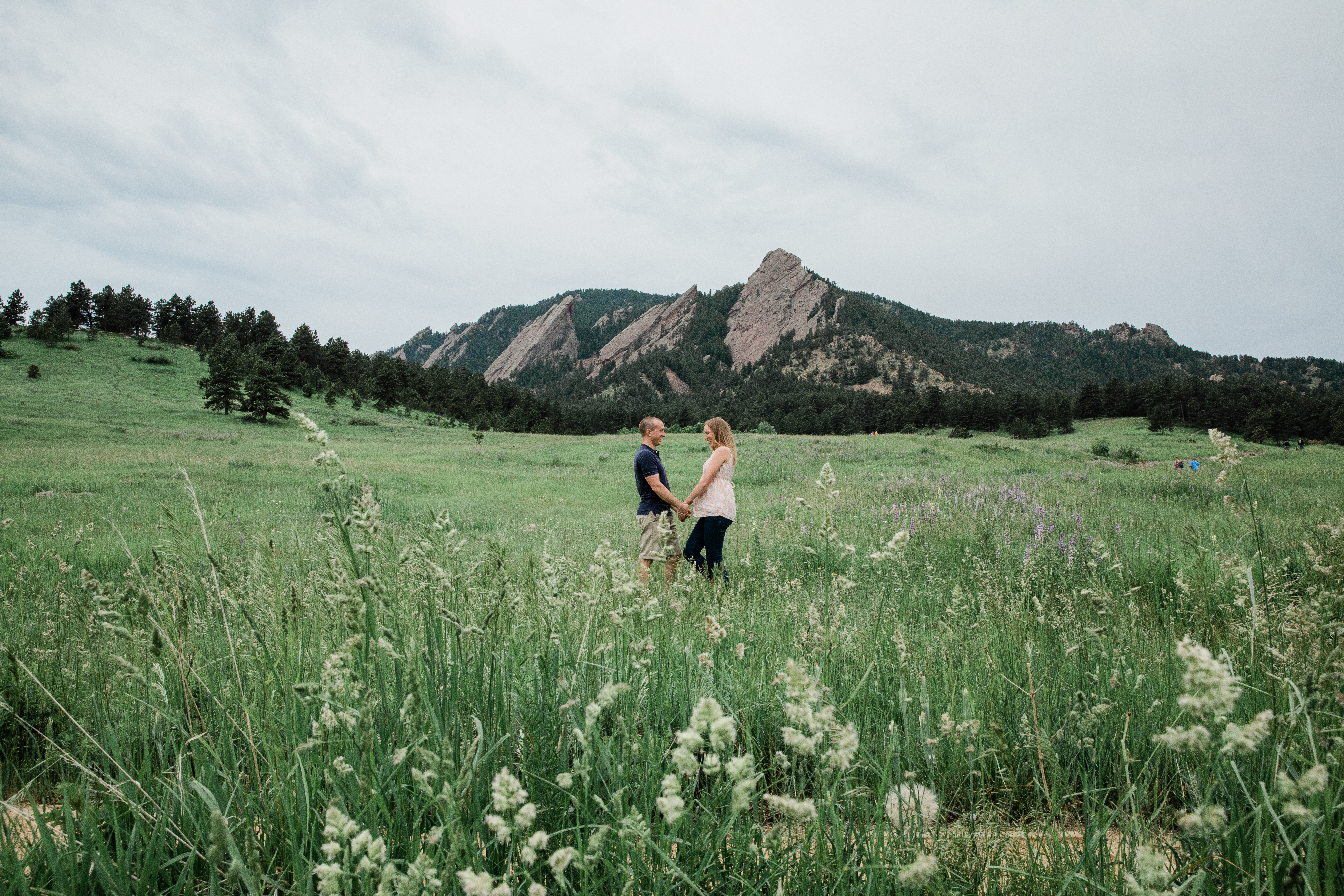 Wide picture of maternity portraits couple in front of the Flatirons in Boulder, Colorado.