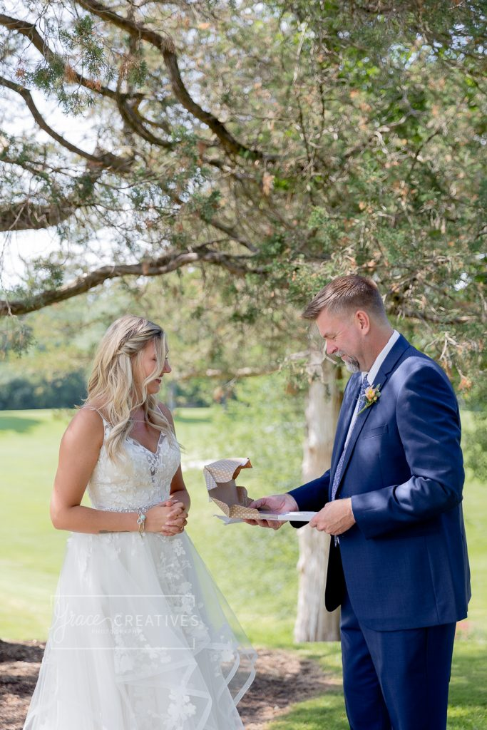 father of the bride opening up a gift outside on his daughter's wedding day at Chenequa country club