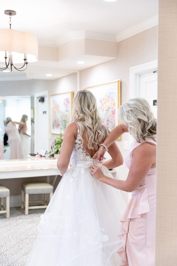 Mother of the Bride helping her daughter get into her wedding dress