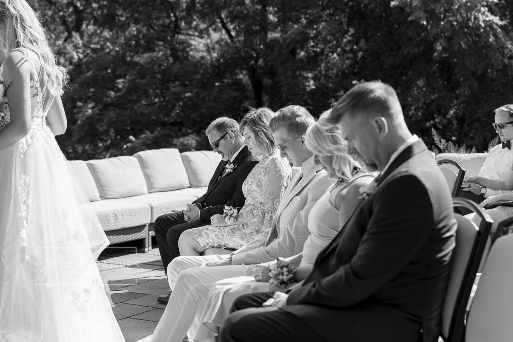 Front row of guests praying during wedding ceremony