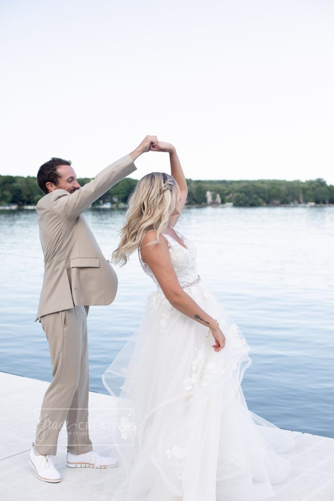 Bride being twirled by the groom on the dock at Cenequa country Club
