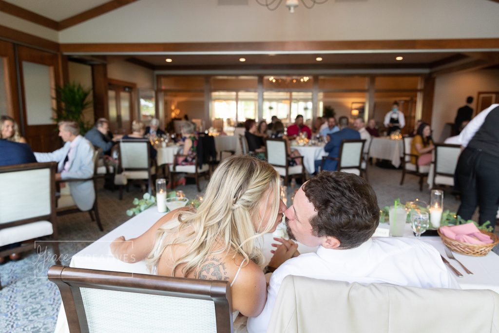 Bride and Groom kissing during Reception Dinner at chenequa country club