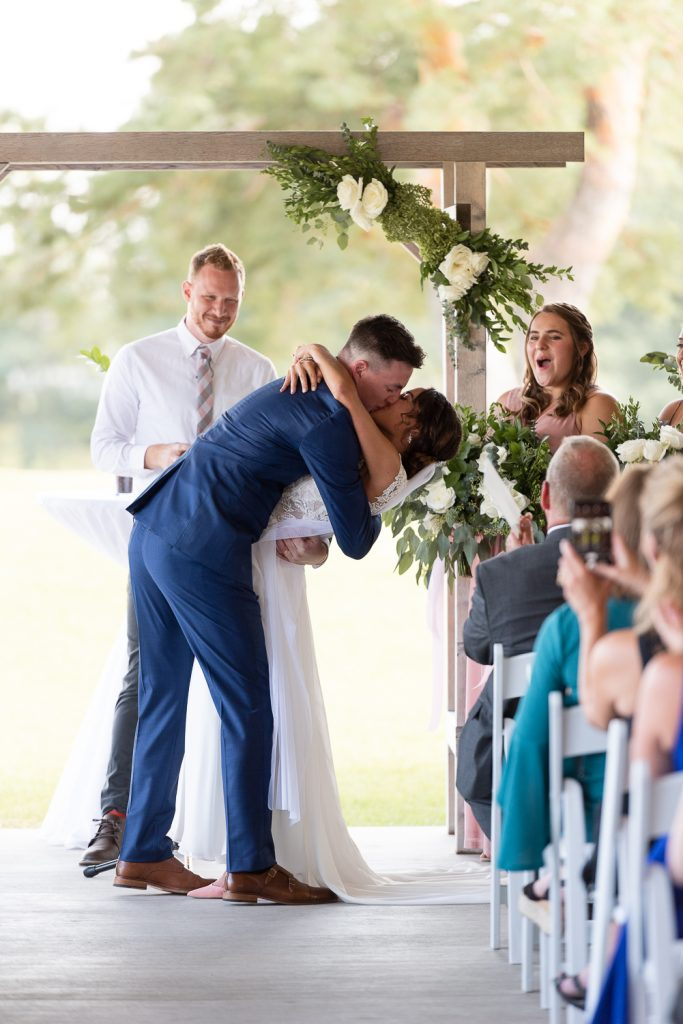 Wedding ceremony first kiss at the Carriage house at Lac La Belle