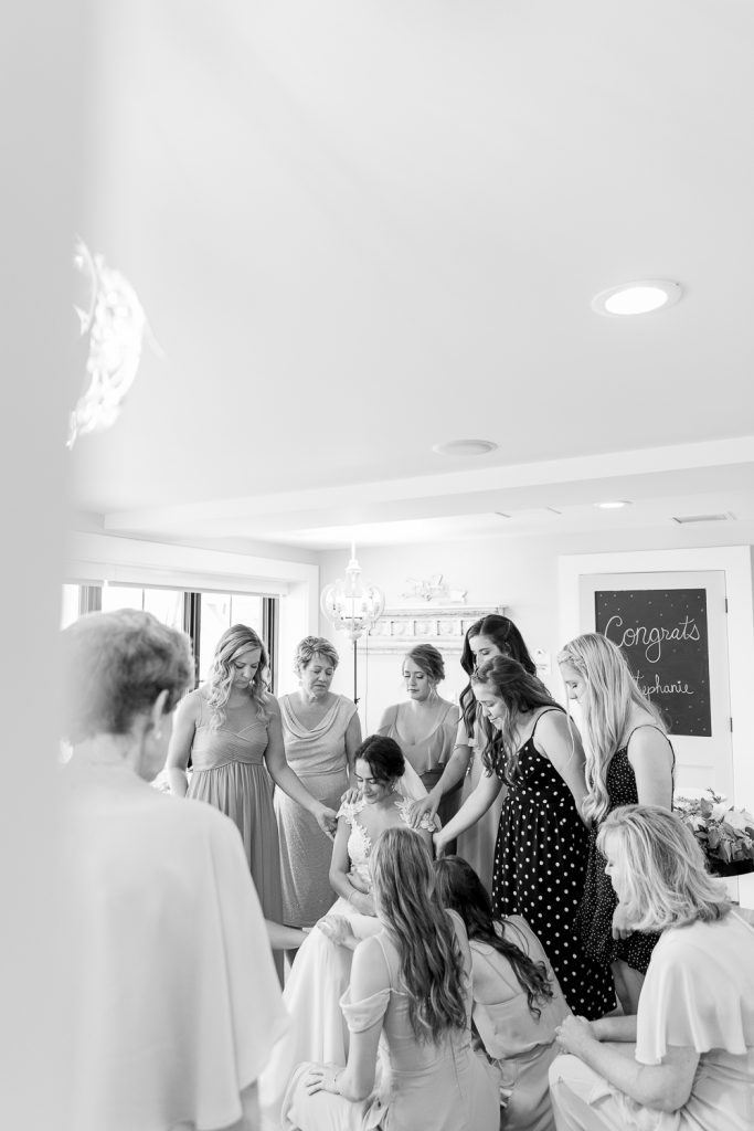 women praying over bride during wisconsin wedding