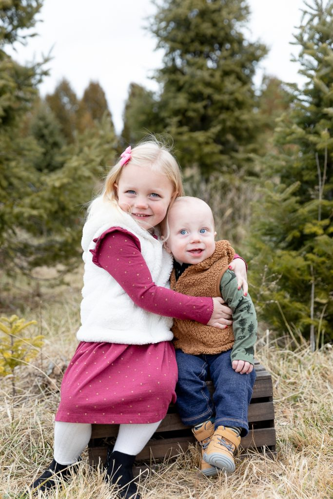 young brother and sister sitting on a crate during tree farm mini session with grace creatives