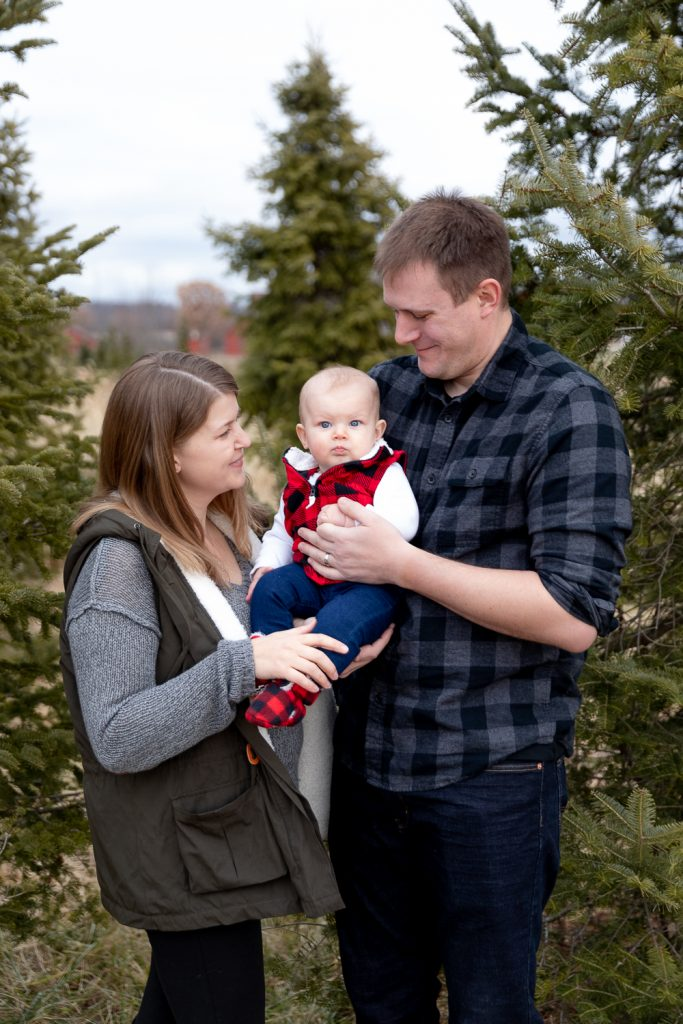 mom and dad holding their daughter in front of an evergreen tree at Poplar creek tree farm