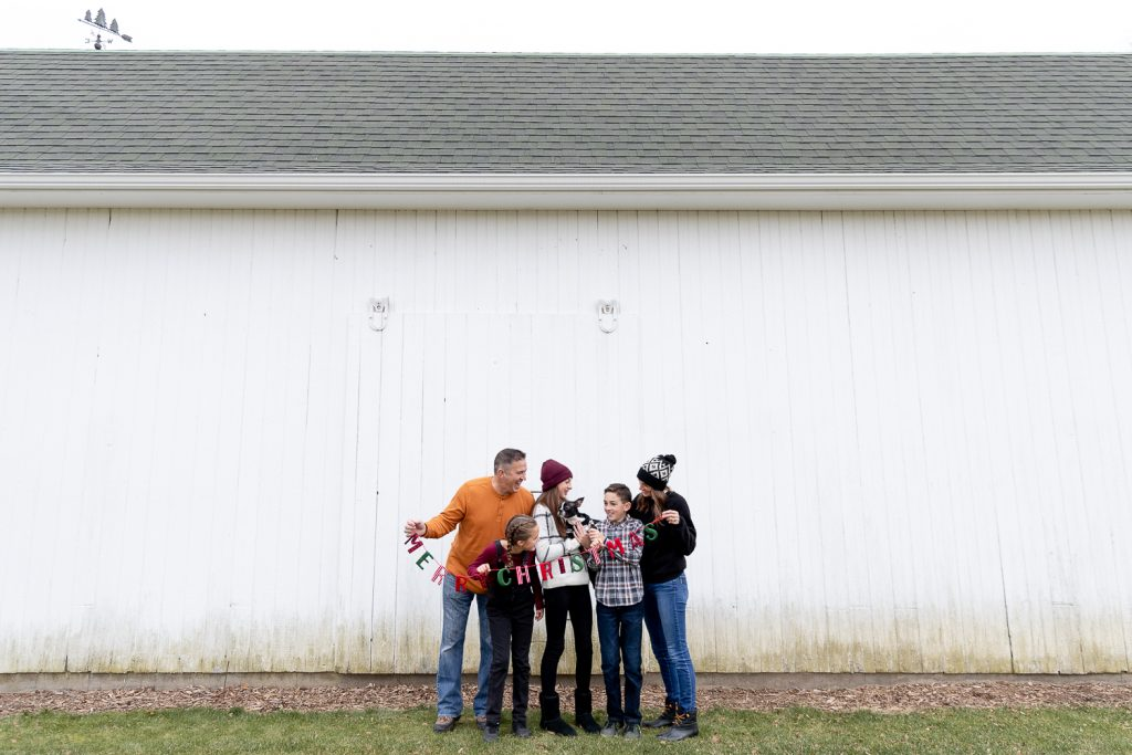 Family of 5 holding a Merry Chirstmas banner in front of a white barn