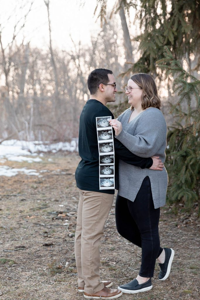 far away shot of new mother and father with strand of ultrasound photos
