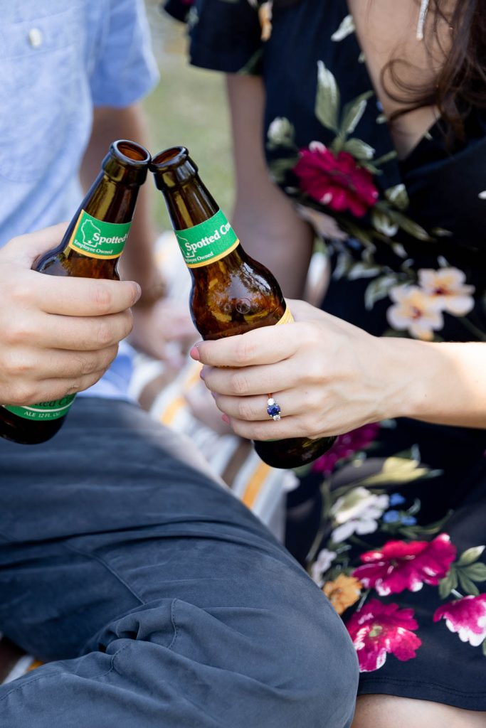 couple clinking their New Glarus Spotted Cow beers during engagement session at Fairchild Botanical Gardens