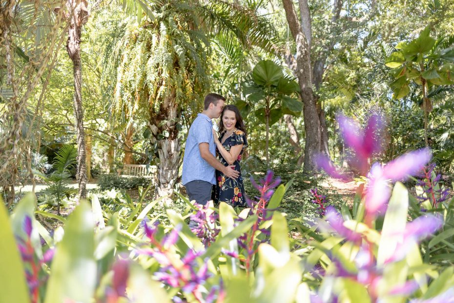 couple standing next to spring flowers during engagement session at Fairchild botanical Gardens
