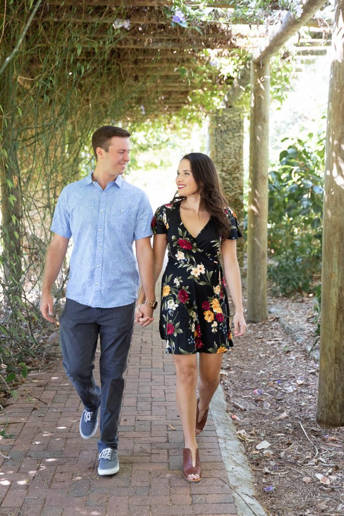 Couple walking hand in hand during Fairchild engagement session in Miami