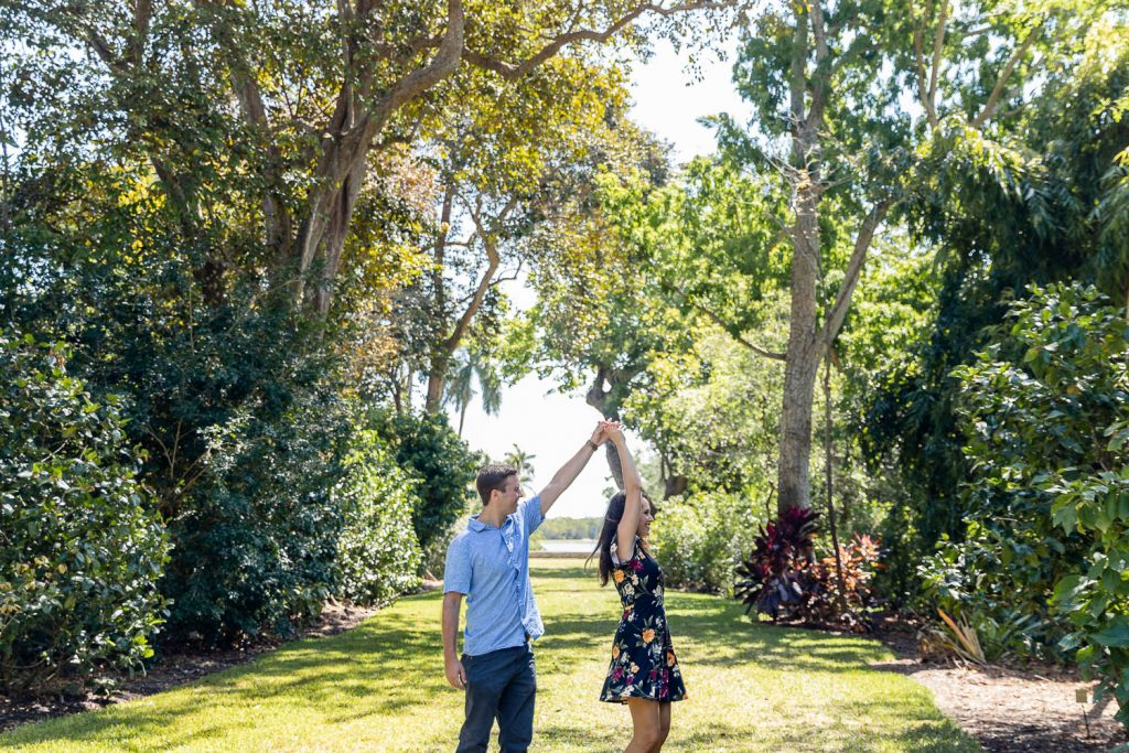 man twirling his girlfriend during engagement session at Fairchild Botanical Gardens with Grace Creatives Photography